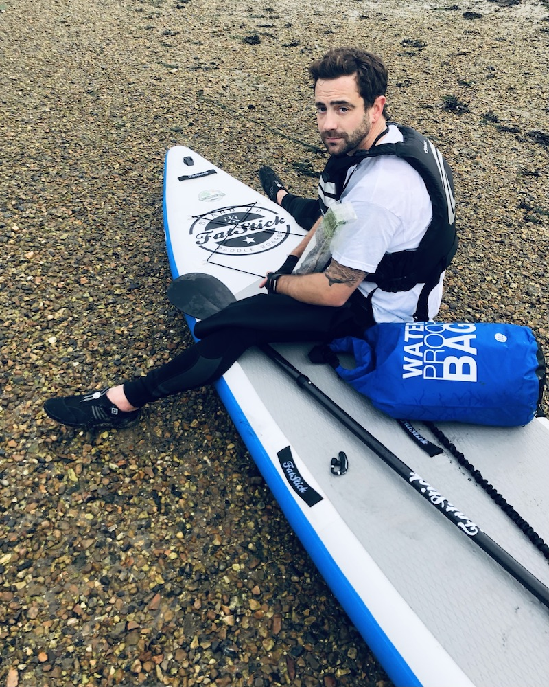 david haze on a beach with his paddle board