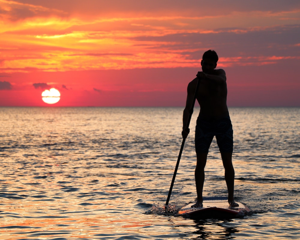 Woman on SuP board sunset